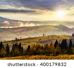 coniferous forest on hillside meadow with fog over rural  valley in autumn mountains in evening light - stock photo