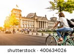 Stock photo urban city life with famous reichstag building in the background in beautiful golden evening light 400634026