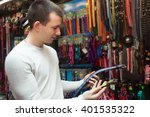 Stock photo young man watching dog leads and smiling in pet store 401535322