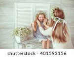 A young girl is sitting on the fireplace. Her mother is tiding her hair. They are both having floral wreathes and casual clothes on. The atmosphere of happiness is all around them.