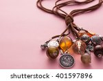 Small photo of High Angle Still Life View of Handmade Artisan Jewellery on Pink Background - Stylish and Funky Necklace Made with Brown Leather and Adorned with Silver Charms, Wood Beads and Stones