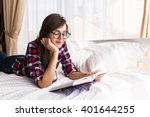 Girl reading a book in bed ...