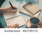Small photo of Woman left hand writing journal on small notebook in outdoor area at cafe with morning scene and vintage filter effect