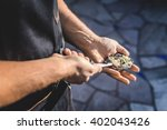 A Man Shucking An Oyster And...