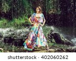 Stock photo beautiful fashion model posing in front of the waterfall 402060262