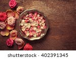 Stock photo pink and white rose petals in silver bowl with water on wooden background 402391345