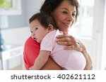 proud grandmother holding baby... | Shutterstock . vector #402621112