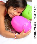 little asian girl with coins and piggy bank - stock photo