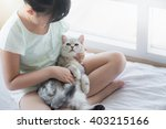 Stock photo beautiful asian girl playing with american shorthair cat on the bed 403215166