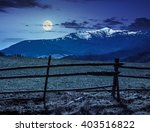 fence on the rural meadow in mountain region in spring time at night in full moon light - stock photo