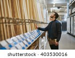 Carpenter selecting wood in a hardware store or warehouse standing looking at cut lengths on a rack, side view