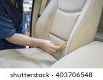Image of worker hand cleaning the car seat with a brush to remove dust or dirt - stock photo
