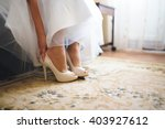 bride putting on wedding shoes... | Shutterstock . vector #403927612