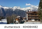 Ski resort, snowy Caucasus mountains, cottages, slope and cable car among trees - stock photo