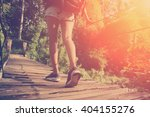 Small photo of Woman's legs with backpack walking across hanging bridge (intentional vintage color and sun glare)