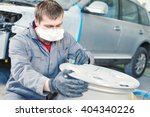 Small photo of repair mechanic worker with light alloy car wheel disk rim