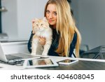 Stock photo beautiful young girl holging her ginger cat devices on the kitchen table 404608045