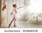 Small photo of Cute little girl dreams of becoming a ballerina. Child girl in a pink tutu dancing in a room. Baby girl is studying ballet.