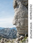 Small photo of Close-up of red indian side face shape monolith grey rock against of beautiful endless mountain chain