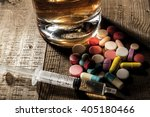 Small photo of Alcohol and pills on table with shadow
