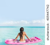 Small photo of Beach vacation relaxation on ocean water bed. Bikini woman from the back sitting on a pink pool floating air mattress looking at horizon of the perfect turquoise pristine sea in tropical destination.