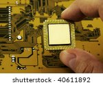 Fingers holding a CPU - stock photo