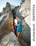 Small photo of Joyful couple standing together near rocks, outdoor. Girl wearing blue dress and man wearing white shirt and claret trousers. Faces very close to each other. Full body