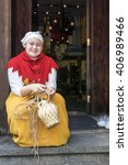 Small photo of TALLINN, ESTONIA - NOVEMBER 6: woman in national costume in front of a famous local restaurant Old Hansa November 6, 2015
