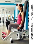 Small photo of Young beautiful Caucasian smiling girl is working out on hip abductor machine in gym
