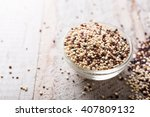 Stock photo pile of mixed raw quinoa south american grain in glass bowls on white rustic wooden background 407809132