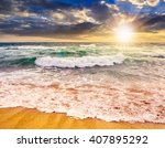 green and mighty sea wave attacks the sandy beach and break on them in evening light - stock photo