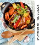 Small photo of Delicious Homemade Colorful Vegetables Ragout with Eggplant, Carrots, Potatoes, Leek, Red Bell Pepper and Green Pea in Black Iron Stewpot with Wooden Spoon and Fork closeup on Blue Napkin
