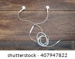 white earphones on wooden... | Shutterstock . vector #407947822