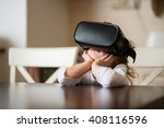 Stock photo child with virtual reality headset sitting behind table indoors at home 408116596