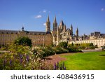 Picturesque ancient abbey of St. Stephen in Caen, like a medieval castle around which there are many lawns with bright blooming flowers in the background of the summer sky in the rays of summer sun.