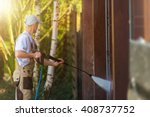 Garage Gate Water Cleaning. Garage Walls and Gate Powerful high Pressure Water Washing. Caucasian Worker Cleaning Building Elements. - stock photo