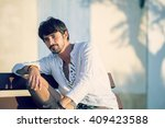handsome young guy sitting... | Shutterstock . vector #409423588