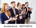 Small photo of Row of impressed young business co-workers clapping a colleague as they stand in a line smiling and offering congratulations