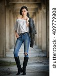 Stock photo portrait of beautiful sexy young woman with modern outfit leather jacket jeans white blouse and 409779808