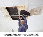 Man Repairing Collapsed Ceilin...