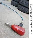 Small photo of Airgun wrench and tires on the ground at automotive service center