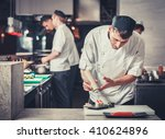 male cooks preparing sushi in... | Shutterstock . vector #410624896
