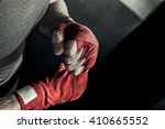 Stock photo closeup male hand of boxer with red boxing bandages fists of fighter before the fight or training 410665552