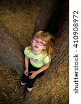Small photo of Cute little girl having a temper tantrum in a tree, pleading she is too tired to walk anymore.