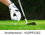 hand putting golf ball on tee... | Shutterstock . vector #410991262