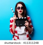 Small photo of portrait of the beautiful young woman with slapstick on the blue background