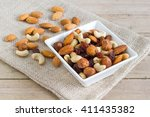 nuts in a white bowl on a sack  ... | Shutterstock . vector #411435382
