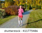woman running in autumn park ... | Shutterstock . vector #411775486