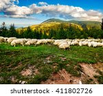 Composite image of rural landscape with flock of sheep on the hillside meadow at the foot of the mountain in Romania - stock photo
