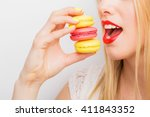 woman eating three macaroons | Shutterstock . vector #411843352